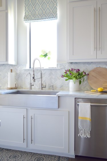 Gray and white tile herringbone backsplash with white cabinets and apron front sink