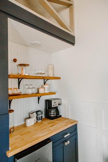 White herringbone backsplash with coffee bar and floating wood shelves