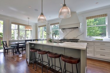 kitchen with white island, hardwood floor, and wooden bar stools