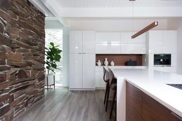 kitchen with white cabinetry and wood accents next to stone wall