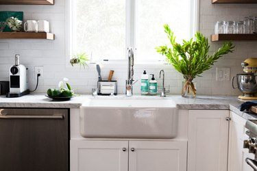 focus on farmhouse sink surrounded by subway tile, stone countertop