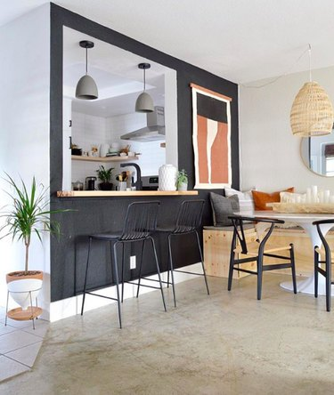 Minimal bohemian dining room with midcentury furniture and black accent wall