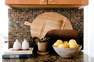 focus on items on a dark granite countertop with a mosaic backsplash