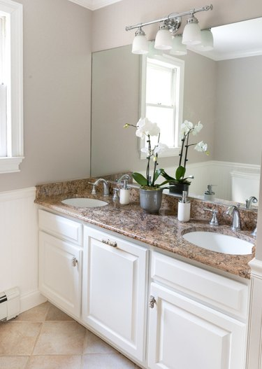 Painted bathroom cabinets before and after featuring white cabinets and stone countertop