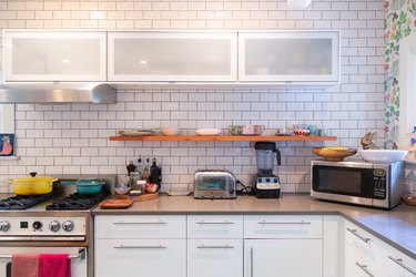 kitchen with subway tile wall, white kitchen cabinets and appliances on the countertop