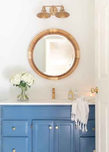 Painted bathroom cabinets before and after featuring nautical decor and blue cabinets