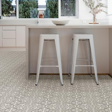 kitchen space with white stools and patterned flooring