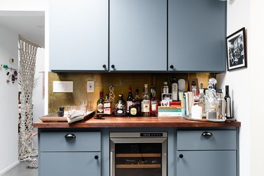 focus on bank of blue cabinets with butcher block counter and wine fridge