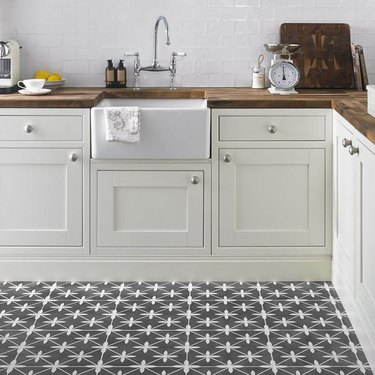 white kitchen with wooden countertops and retro gray flooring