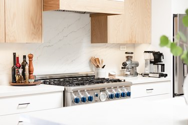 focus on kitchen stove surrounded by marble-effect stone
