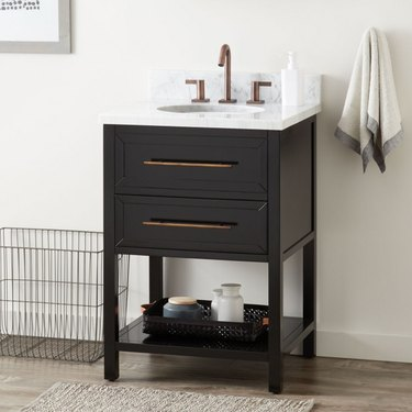 Black small bathroom vanity with large drawer pulls and quartz countertop