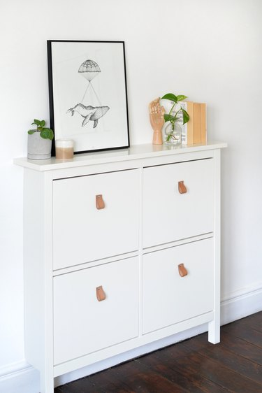 White IKEA shoe storage cabinet with framed poster, books and decorative items.