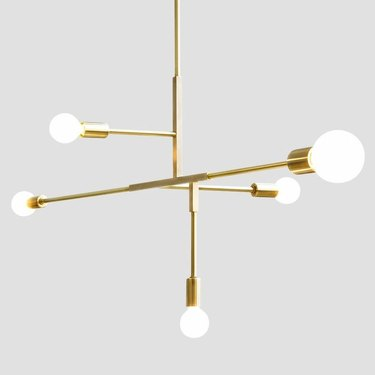 Brass pendant light with five straight arms in horizontal and vertical directions at varied heights. White globe lights on the end of each arm