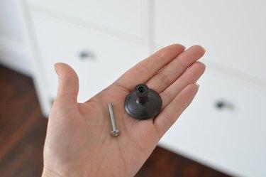 Hand holding metal bolt and black IKEA door handle.