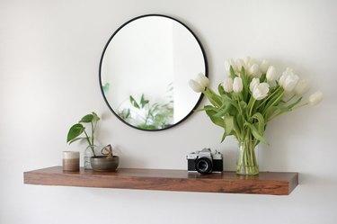 dark brown entryway floating shelf with circular mirror hanging above it.