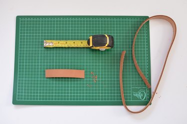 Green cutting mat, measuring tape and leather belt.