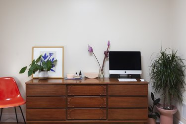 dresser with framed art and computer monitor