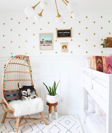 All-white child's room with gold triangle wall decals, midcentury pendant light, rattan chair, and white bunkbeds