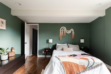 green bedroom with wood floors, white bed, artistic quilt