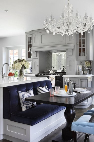 chandelier and navy velvet kitchen island with bench seating