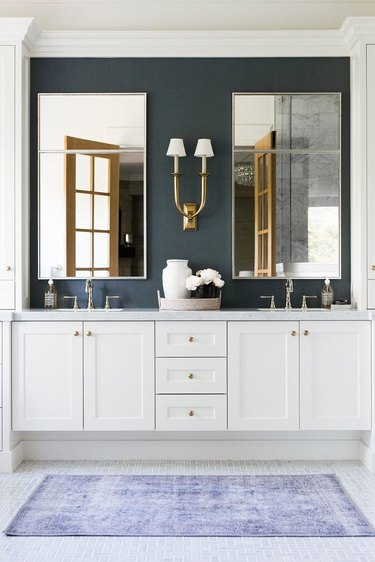 White Bathroom Cabinet with navy blue accent wall by Studio McGee