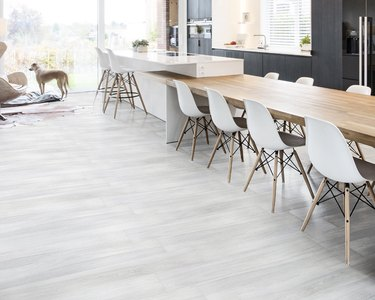 kitchen and dining space with wood table, black cabinets, and white chairs with light porcelain tile floor
