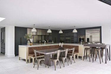 kitchen island with bench seating in modern and industrial kitchen with wood island and metal chairs
