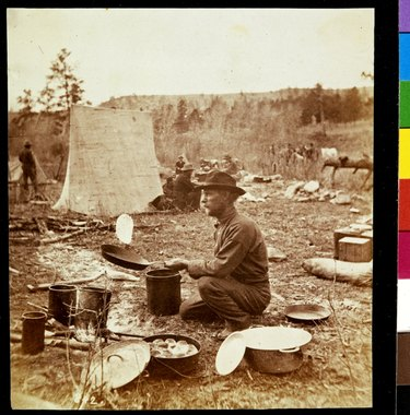 A man cooking flapjacks in a frying pan next to a Dutch oven outside
