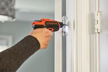 Installing hinge screws.