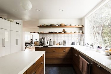 white kitchen dark floors with wood lower cabinets and open shelving