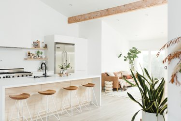 large airy kitchen with wood beam overhead and white waterfall countertop