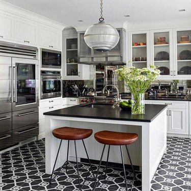 Black kitchen floor featuring black and white tile and modern styling