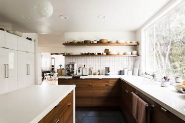large kitchen with window looking toward trees, dark cabinetry and white counters
