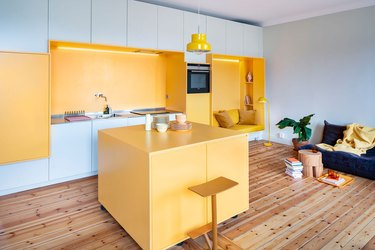 open concept yellow living room and kitchen