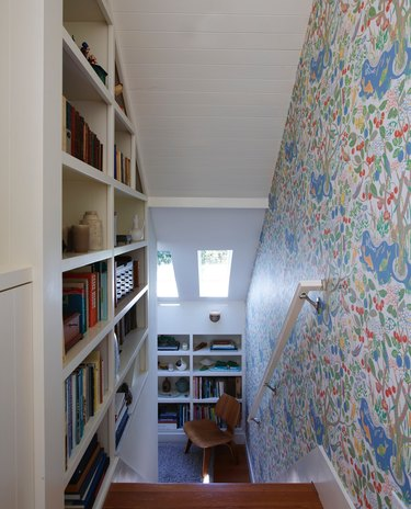 Staircase with bookcase and floral wallpaper down to room with skylights
