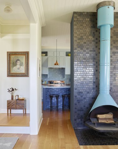 FireHOOD fireplace against black Heath tile with kitchen in the background