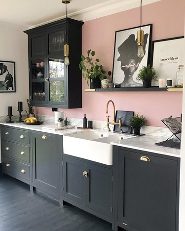 Black kitchen floor in painted wood and featuring a pink wall and modern decor