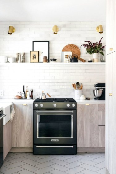 white and black kitchen cabinet hardware idea with brass hardware and white subway tile backsplash