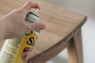 Spraying coat of shellac on table