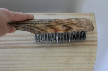 Scrubbing raw wood with wire brush