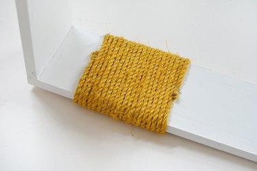 Yellow sisal rope wrapped around white wood