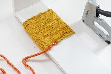 Yellow and orange sisal rope wrapped around white wood