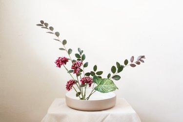 diy ikebana flower arrangement of burgundy flowers and long green leaves
