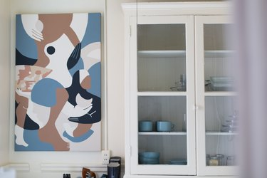 focus on glass-doored cabinet with cups and mugs inside next to abstract artwork