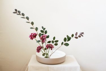 burgundy flowers and leaf stems inserted into flower frog inside shallow bowl