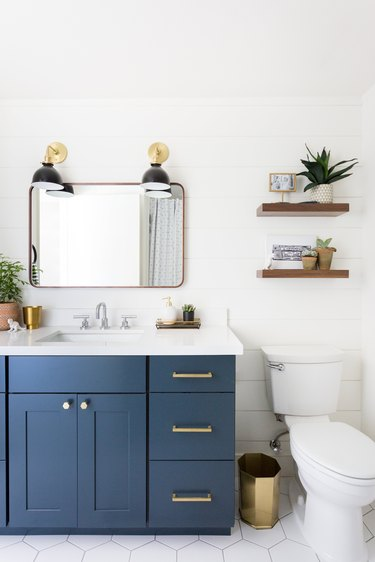 white and blue bathroom cabinets with wooden and brass accent