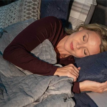 woman sleeping with a gray blanket and a few pillows nearby