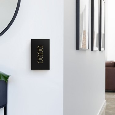 black light switch on white wall with hallway and framed art in the background