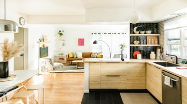 open kitchen looking into living room with light wood cabinetry and a wall with black tile