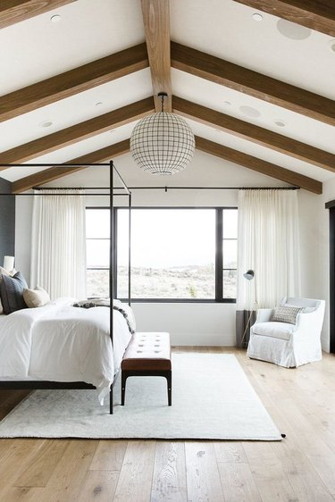 rustic bedroom with chandelier and exposed wood beams